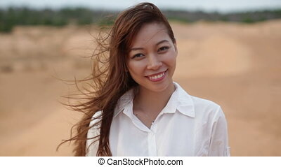 Asian woman smile outdoor desert wind blowing hair, wear...