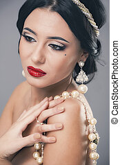 Beautiful woman with curly hair and evening make-up. Jewelry and Beauty. Fashion art photo