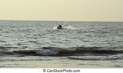 Young guy cruising on a jetski at sunny day