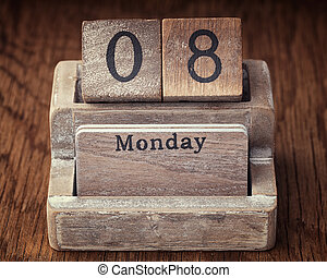 Grunge calendar showing Monday the eighth on wood background