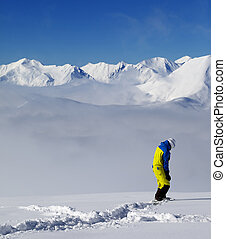 Snowboarder on off-piste slope with new fallen snow Caucasus...