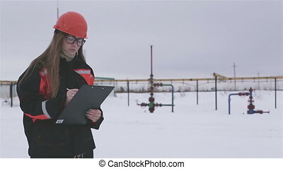 Female engineer working in an oilfield - Female engineer and...