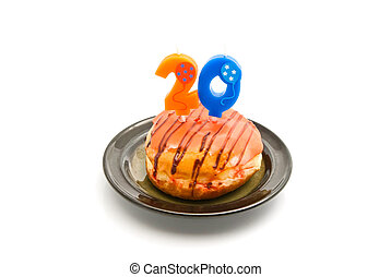donut with twenty years birthday candle on white background