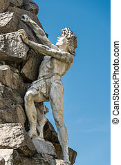 statue of a man climbing a rock - useful for concepts