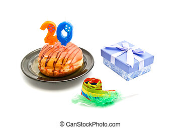 donut with twenty years birthday candle, whistle and gift on...