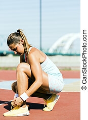 Athlete tying shoe lace with both hands in summer