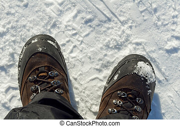 Snow boots - Foot gear. Pair of winter boots on snow.