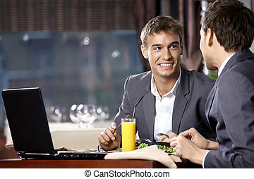 Business supper - Two young businessmen have supper at...