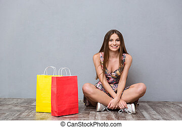 Beautiful smiling girl sitting on the floor with legs...