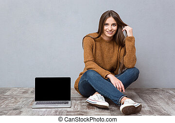 Happy woman sitting on floor near laptop with blank screen