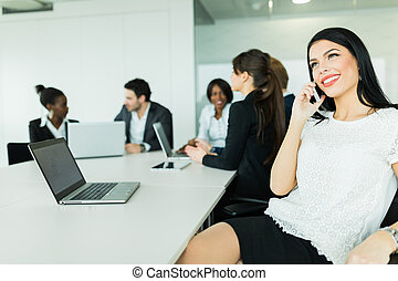 Beautiful young businesswoman smiling and happily talking during business brainstorming