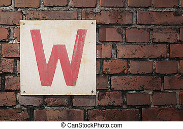 W - Old sign with letter W on a brick wall