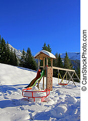 Playground covered in snow - A roundabout, swing, playground...