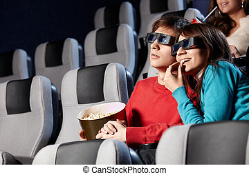At a cinema - The couple with pop-corn looks cinema in 3d