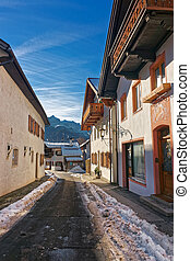 Sunlit narrow street in Garmisch-Partenkirchen, Germany. It...