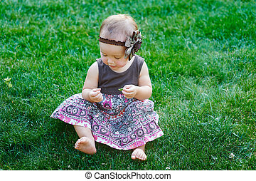 Cute little girl sitting on the grass on a sunny summer day