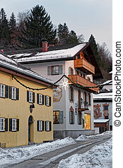 Snowy street of Garmisch-Partenkirchen with unique murals on...
