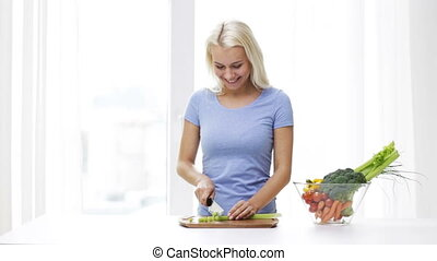 smiling young woman chopping celery at home - healthy...