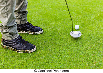 Hitting a golf ball with a putter - a golf player aiming for...