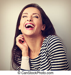 Laughing young casual woman with wide open mouth and closed...