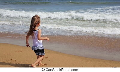Little  Girl playing with waves at the beach
