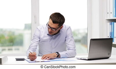 busy businessman with laptop and papers in office