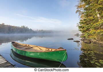Green Canoe Tied to Dock on a Lake in Autumn - Ontario,...