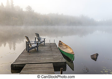 Green Canoe and Dock on a Misty Morning - A green canoe tied...