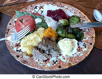 Thanksgiving dinner plate with many assorted dishes ready to...