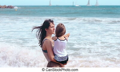 Mother and daughter hug kissing on the sea beach