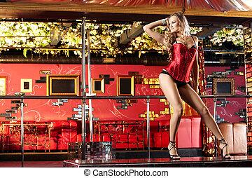 Striptease - The attractive girl dances a striptease in club