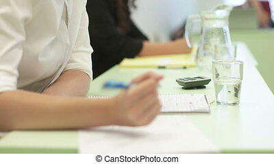 College Team Debates - Shot of students writing down notes,...