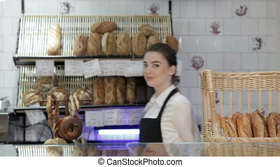 Woman baker smiling new buyer. Young smiling baker inside...