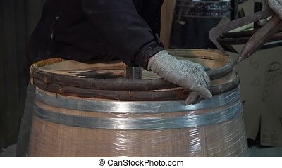 manufacturing wine barrels - laying a finishing strapping