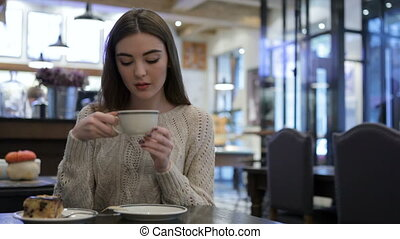 Attractive girl holding a cup of coffee. The girl or woman...