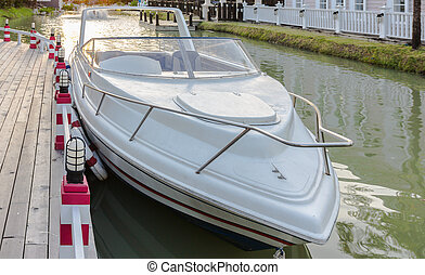 A white speedboat docked on a river