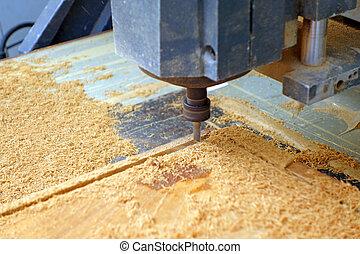 drill machine drilling a wood board