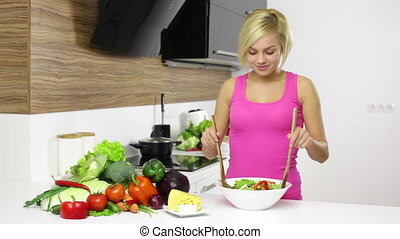 Smiling woman mixing a salad in her kitchen, young blond...