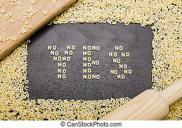 """The answer """"yes"""" made up of a set of words """"no"""", with small pasta letters on a dark background wooden board surrounded by other letters of the alphabet"""