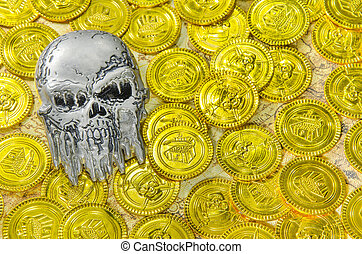 a steel pirate skull on a pirate golden coins