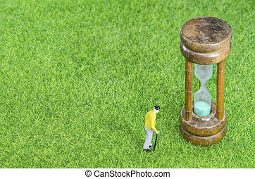 oldman with hourglass - Mini toy oldman standing on a grass...