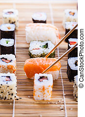Tasty sushi - a salmon nigiri sushi being picked up with...