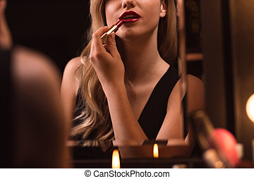 Flirtatious female using red lipstick - Close-up on a...