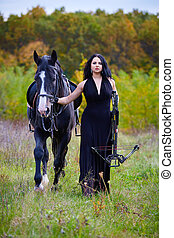 Woman with horse and crossbow in the forest - Beautiful...