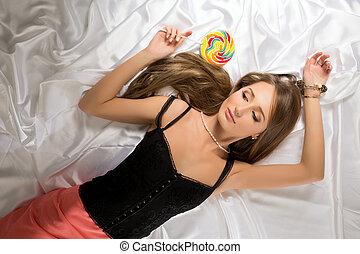 Top view of sexy young coquette with lollipop - Top view of...