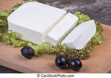 Traditional white greek cheese on a wooden board Close up