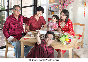 Celebrating Chinese New Year, reunion dinner. Happy Asian Chinese multi generation family with red cheongsam selfie while dining at home.