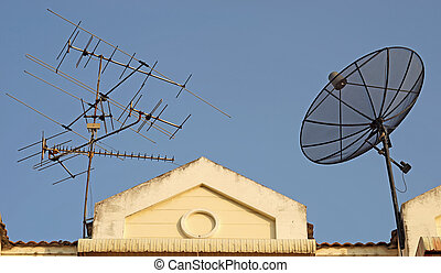 satellite dish and television antenna on roof with beautiful...