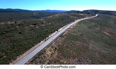 Cyclist climbing mountain road - Aerial view of cyclist over...