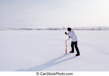 winter fisherman with ice screw on frozen lake - winter...
